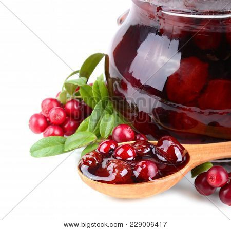 Close Up Of Cowberry Jelly In Wooden Spoon And In Jar With Fresh Berrys On A White Background