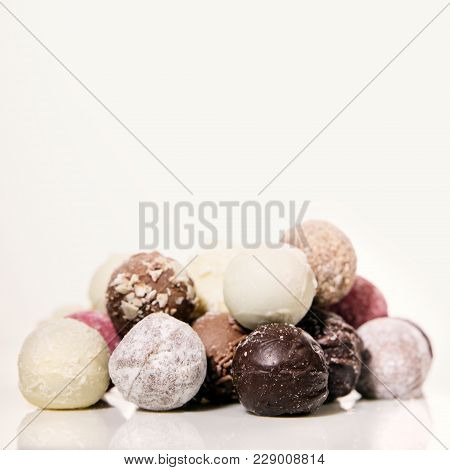 Chocolate Pralines Or Truffles In Front Of White Background With Copyspace