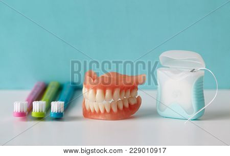 Dental hygiene. Dental floss with toothbrush and dentures.