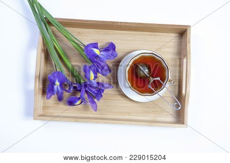 Violet Irises Xiphium -bulbous Iris, Sibirica- With Cup Of Tea On White Background With Space For Te