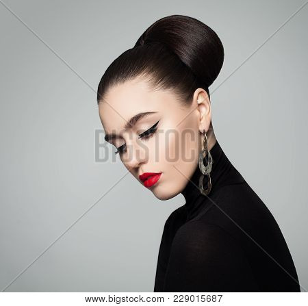 Elegant Young Woman With Hair Bun Hairstyle And Eyeliner Make Up. Female Model Wearing Black Roll Ne