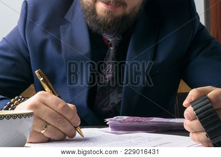 Business Man Lawyer With Wristwatch Writing Contract At The Table, Drink Cofee And Working On Docume