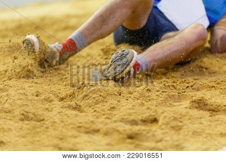 Sportsman Landing Into Sandpit In Long Jump Competition. Track And Field Competitions Concept Backgr