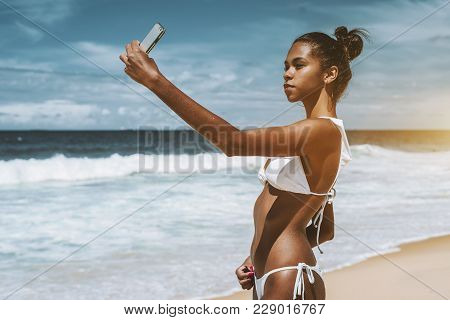 Charming Young Brazilian Girl Is Taking Selfie Using Front Camera Of Her Cellphone While Standing On