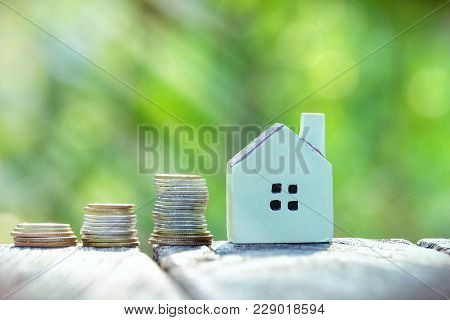 A Row Of Coins And House Model On The Old Wooden Background  With Sun Beams And Green Nature Backgro