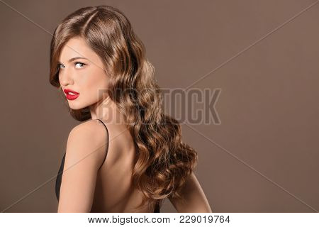 Beautiful young woman with long wavy hair on color background