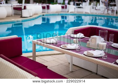 Beautiful Table Setting With Crockery For Party In Open Air Restaurant Near Pool. Glassware And Cutl