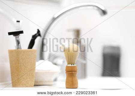 Shaving brush with foam and razors for man on sink