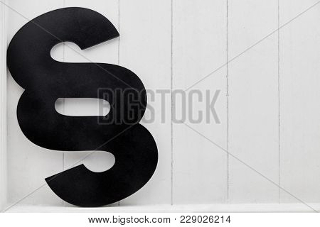 Black paragraph as law concept icon in front of a light wood background