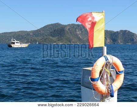 Red-yellow Flag And Lifebuoy On The Beach In The Aegean Sea. Life Ring On The Coast