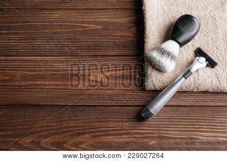 Shaving brush, razor for man and towel on wooden background