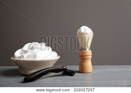 Barber brush, shaving foam and razor for man on table against grey background