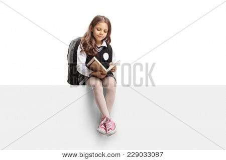 Schoolgirl seated on a panel reading a book isolated on white background