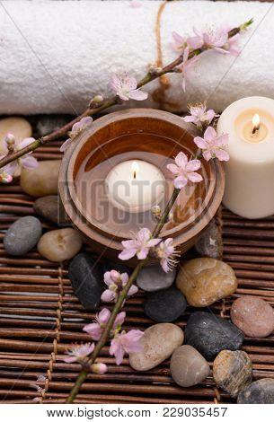 Spa setting with candle ,cherry ,towel, bowl,stones ,candle, on mat