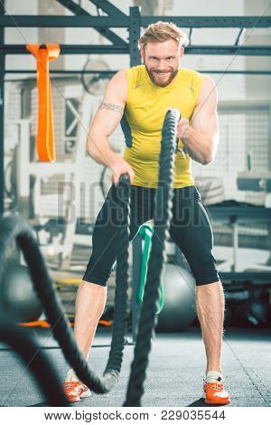 Full length low angle view of a handsome bodybuilder exercising with heavy battle ropes during intense functional training workout at the gym