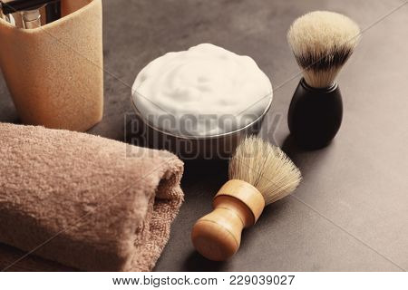 Barber brushes, towel and shaving foam for man on table