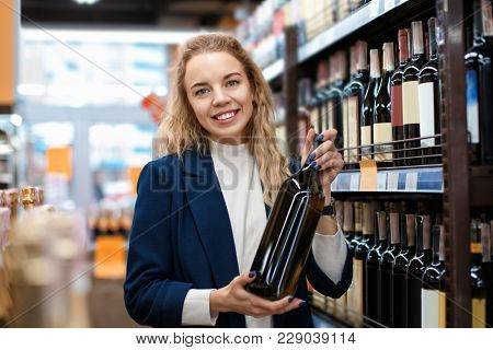 Young woman with bottle of wine in liquor shop. Small business owner