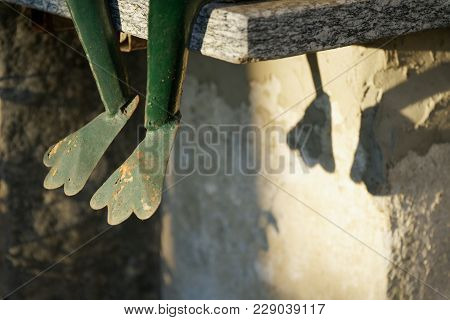 Steel Green Frogs Legs Sits On Stone Stairs. Garden Statue Selective Focus On The Face Of Frog
