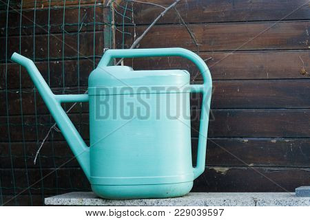 Old Blue Plastic Watering Can On Wooden Background