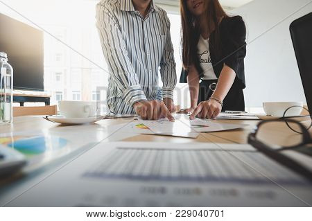 Businesswomen And Freelance Worker Poiting At Data Report Paper On Table In Meeting Room. Startup Bu