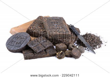 Various Black Pu-erh Chinese Tea With Special Knife On A White Background. Leaves Undergoes Double F