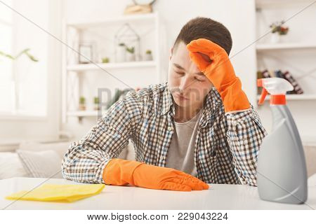 Young Man In Rubber Gloves Tired After Spring-cleaning, Sitting At Table With Rag And Detergents In