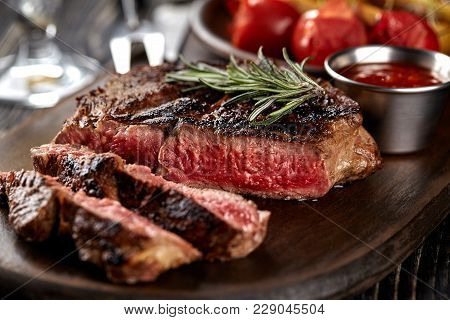Juicy Steak Medium Rare Beef With Spices On Wooden Board On Table. Dry Aged. Served With Potatoes An
