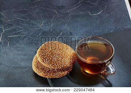 A Transparent Glass Cup Of Delicious Black Tea Or Earl Grey With Cookies On A Dark Greyish Marble Ba