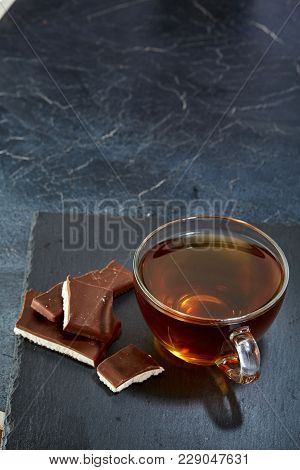 A Transparent Glass Cup Of Delicious Black Tea Or Earl Grey With Chocolate On A Dark Greyish Marble