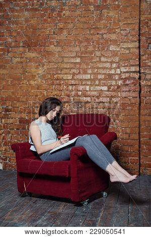 A Teenager Girl Writes In A Diary Notebook Sitting In An Old Chair On A Gloomy Abandoned Station Wit