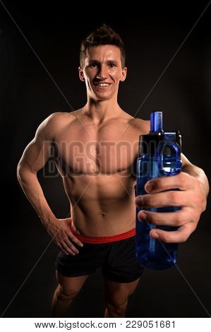 Sportsman With Sport Bottle On Dark Background. Man Athlete Smile With Fit Torso, Body. Thirst, Dehy