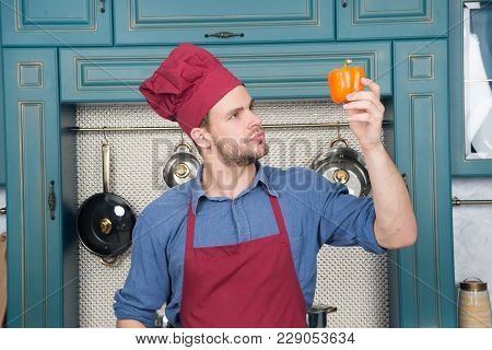Chef Look At Sweet Pepper In Kitchen. Cook Man In Red Hat, Apron With Vegetable. Vegetarian, Health,