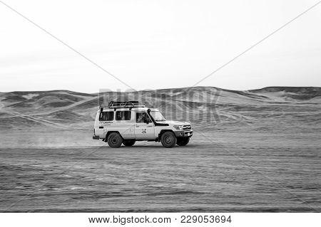Hurghada, Egypt - February 26, 2017: Jeep Driving In Sand Dunes In Desert On White Sky Background. S