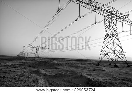 High Voltage Power Lines In Desert Valley On Blue Sky Background. Electricity Distribution Stations