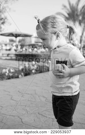Boy Or Adorable Child, Small Little Kid With Blond Hair Ponytail In Tshirt And Blue Shorts Playing W