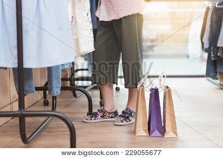 Cropped Image Of Kid Standing Near Hanger With Clothes In Shop