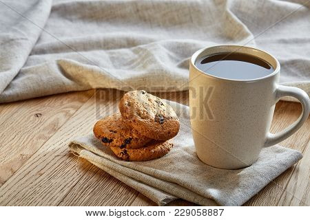 Porcelain Teacup With Chocolate Chips Cookies On Cotton Napkin On A Rustic Wooden Background, Top Vi