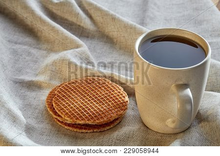 Porcelain Teacup With Waffles On Cotton Napkin On A Rustic Wooden Background, Top View. Delicious Mo