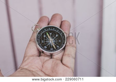 Hand Holding Compass Over Wooden Wall For Business Direction And Travel Concept