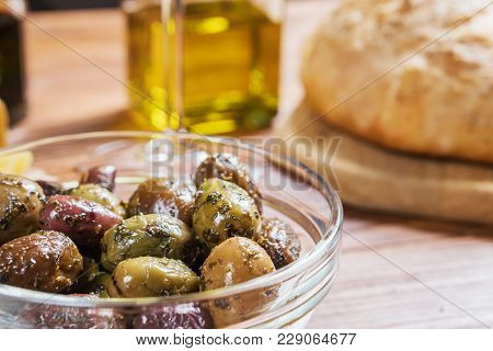 Glass Bowl With Different Kind Of Olives And And Fresh Bread Ciabatta On Wooden Table.