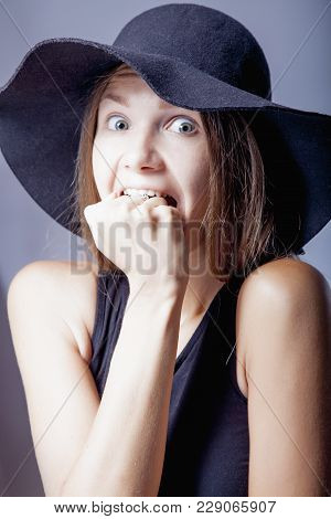 Portrait Of Young Woman Biting Her Fist As Symbol Of Fear And Horror. (gestures, Body Language, Psyc