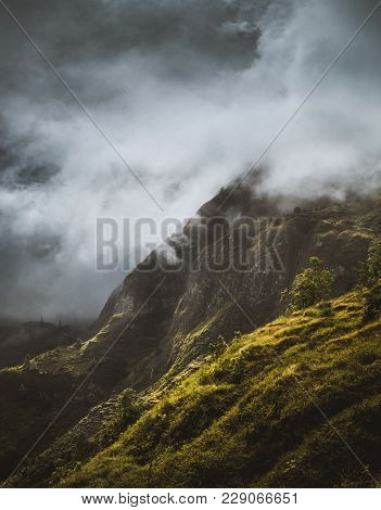 Stunning Scenery With Mist Flowing Over Huge Mountain Slope And Spilling Into The Green Valley. Sant