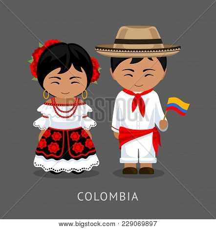 Colombians In National Dress With A Flag. Man And Woman In Traditional Costume. Travel To Colombia.