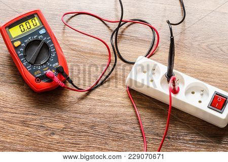 Measurement Of Voltage In Electrical Socket Extension Cord With Multimeter On Wooden Floor Backgroun