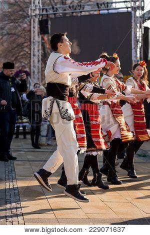Pernik, Bulgaria - January 26, 2018: Male Dancer In Bulgarian Folklore Costume Jumps High While Lead