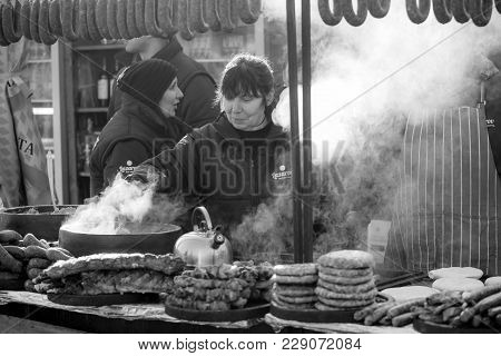 Pernik, Bulgaria - January 26, 2018: Woman Smiles And Cooks Steamy Meal Outdoors In The Sunny Winter