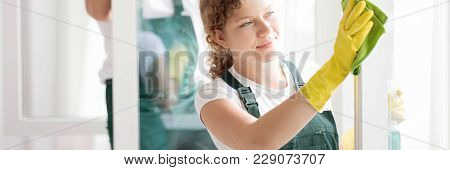 Happy Member Of A Cleaning Crew Wiping A Window Frame In An Apartment
