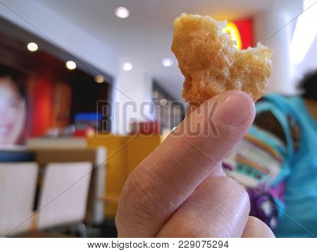 Close-up Chicken Nugget In A Hand At Restaurant
