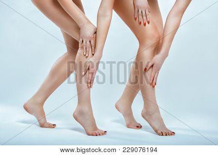 Depilation. Slender Female Feet. Two Women. Photo In The Studio
