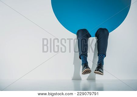 Low Section Of Stylish Young Man Falling Into Hole On Grey